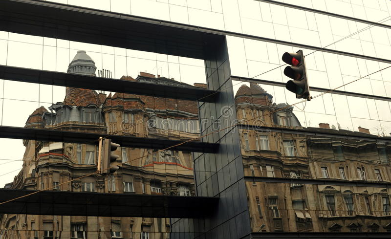 Artistic reflection of old buildings on a new one stock photos