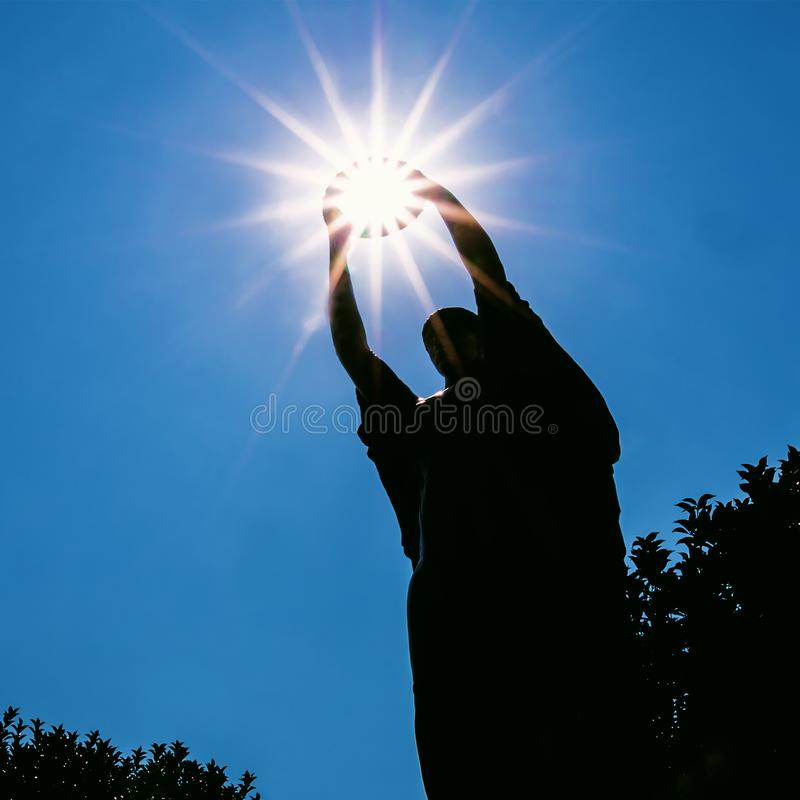 Conquering the Sun. Artistic shot statue in the north of Italy which seems as it`s holding the Sun stock photography