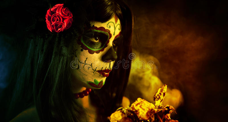 Artistic shot of sugar skull girl with dead roses. Selective focus on rose royalty free stock photo