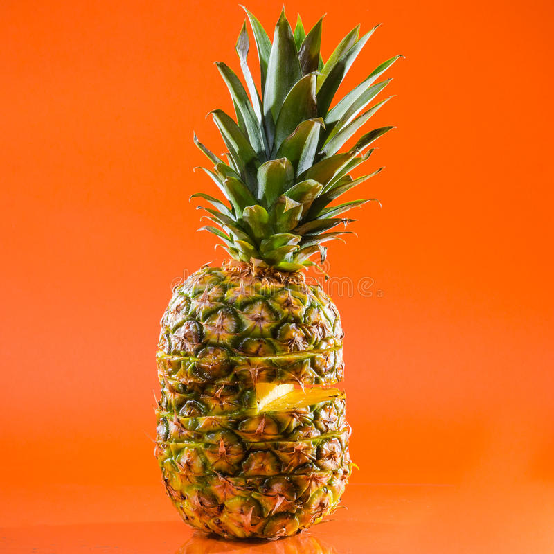 Artistic sliced, standing pineapple on orange background, square shot royalty free stock images