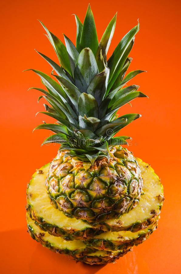 Artistic sliced, standing pineapple on orange background, vertical shot royalty free stock photos