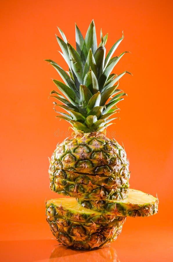 Artistic sliced, standing pineapple on orange background, vertical shot royalty free stock photo