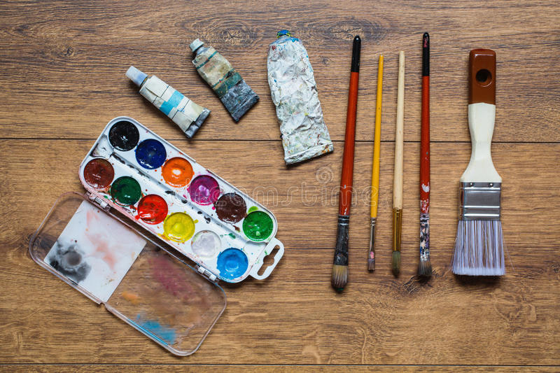 Artistic squirrel brushes, tubes of oil paints and watercolors on a wooden background stock image