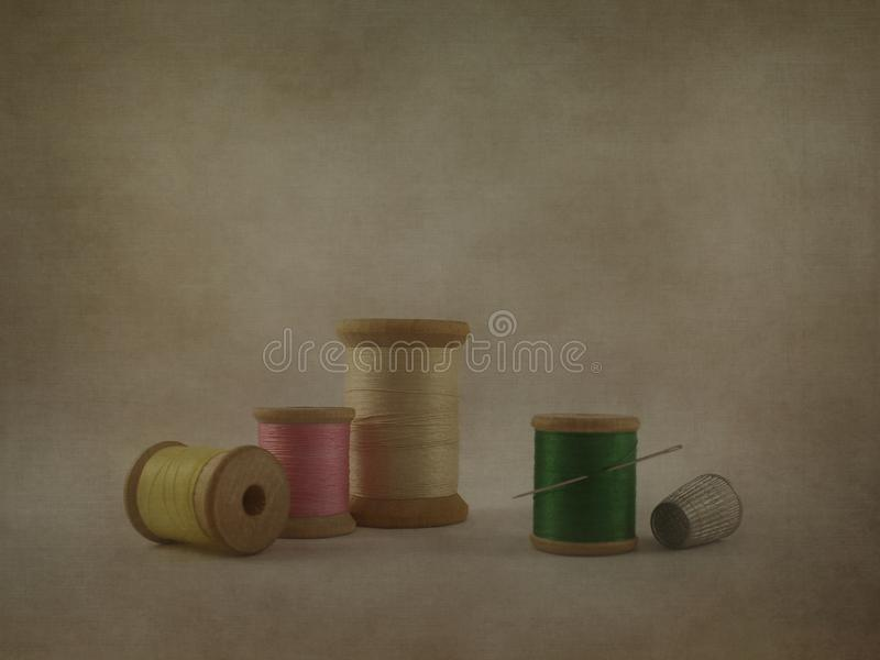 Vintage style colorful wood thread spools, needle, and sewing thimble on textured vignette background with copy space stock photos