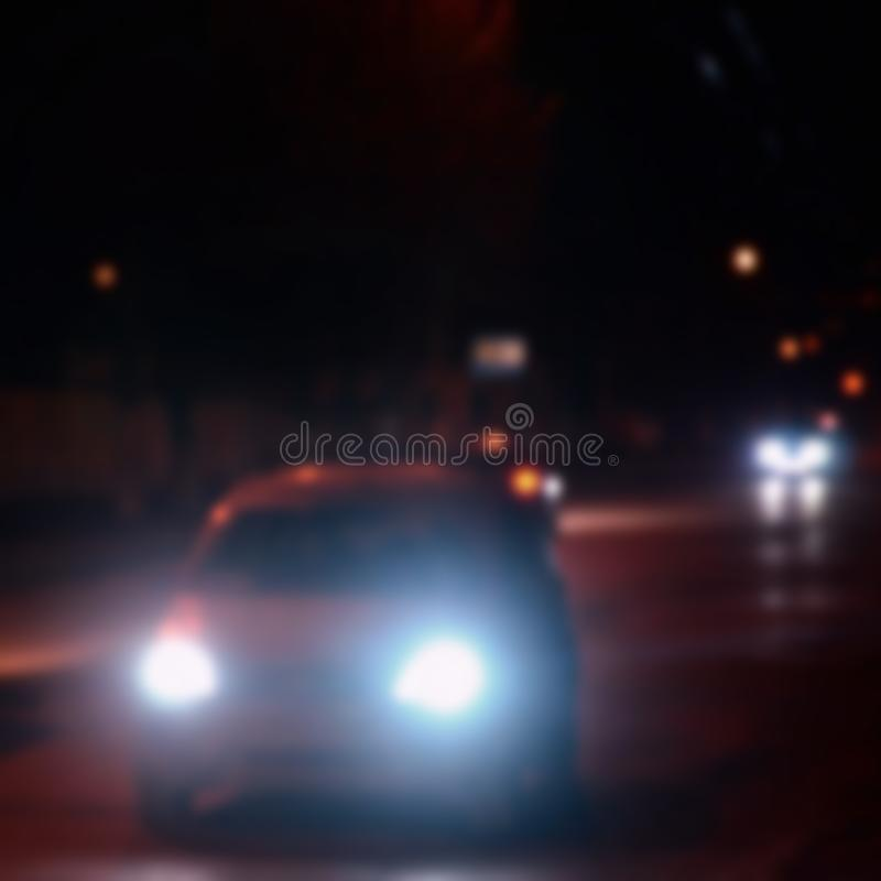 Artistic style - Defocused urban abstract texture, blurred background with bokeh of city lights from car on street at night, vint. Age or retro color tone stock image