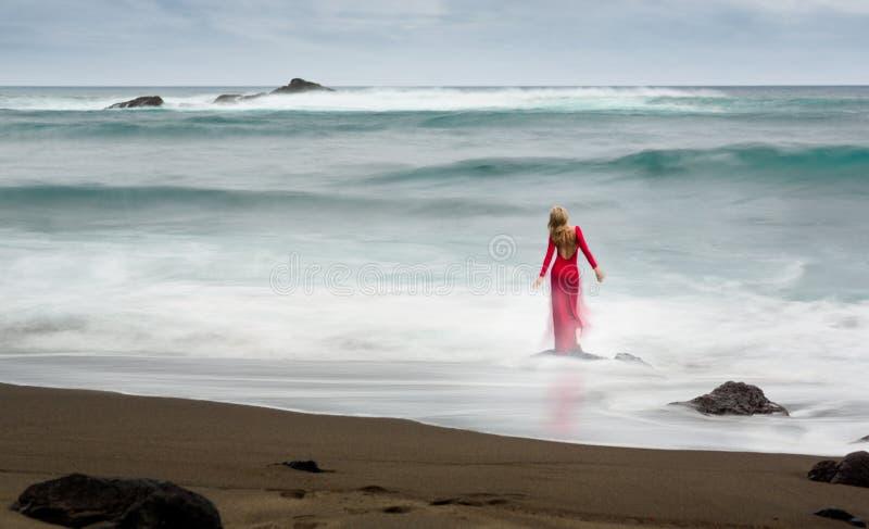 Artistiek fijn kunstbeeld over een rode, lange geklede mooie blondevrouw, die zich op een strandrots in het water bevindt stock foto's