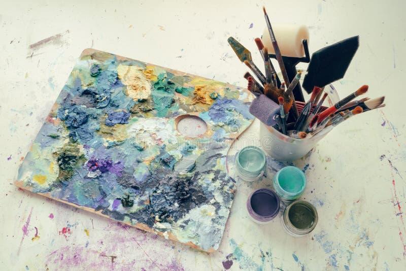 Artistiek materiaal: schilderspalet, verfborstels, verven en palet knifes royalty-vrije stock foto's