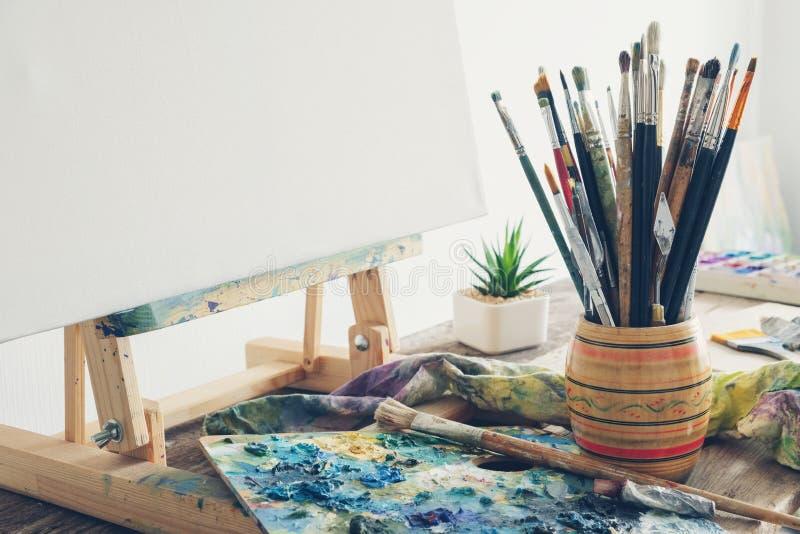 Artistiek materiaal in studio: canvas op houten schildersezel, verfborstels, verven en gebruikt palet royalty-vrije stock foto's