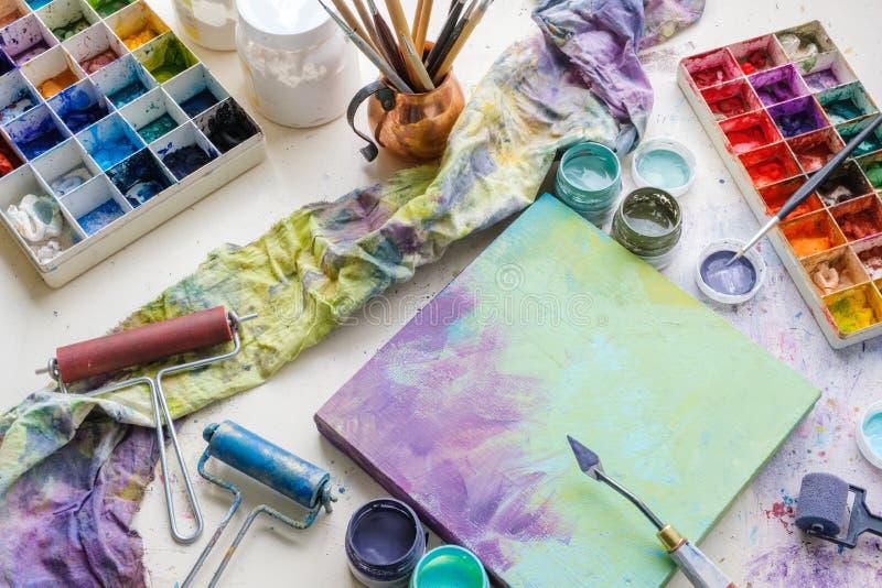 Artistiek materiaal in studio: canvas, paletmes, verfborstels, verven en palet royalty-vrije stock fotografie