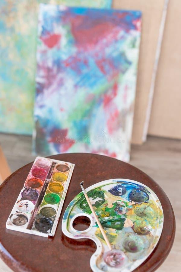Artistiek materiaal in studio, schildersezel, penselen, buizen van verf, palet en schilderijen op de lijst van de het werkkunsten royalty-vrije stock foto's