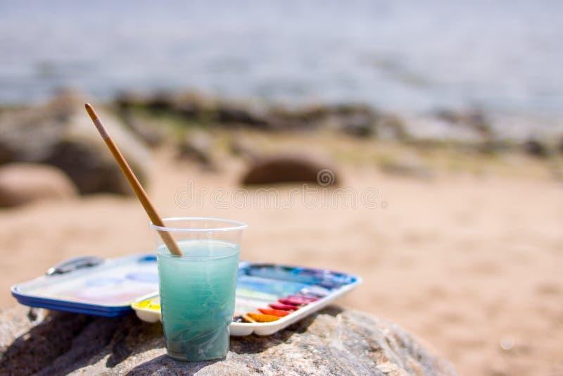 Artistiek materiaal: verfborstels, buizen van verf, palet en schilderijen op rots in aard overzeese kust bij zonnige de zomerdag  stock afbeeldingen