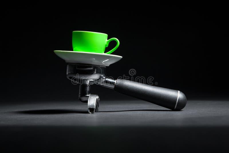 Artistieke die studio van houder voor koffiemachine en groene kop wordt geschoten; stock foto