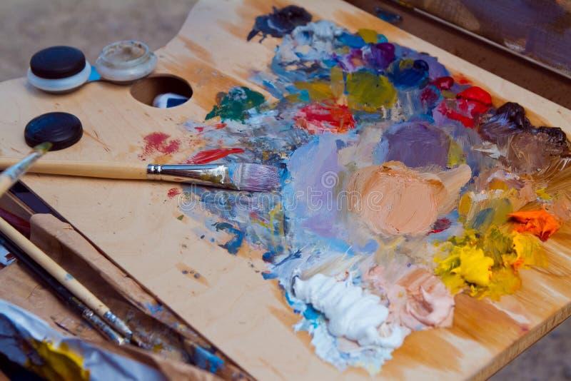 Artistieke die wanorde na plainair het schilderen zitting, de borstels van de schilder met verschillende kleurenolieverven worden royalty-vrije stock foto's