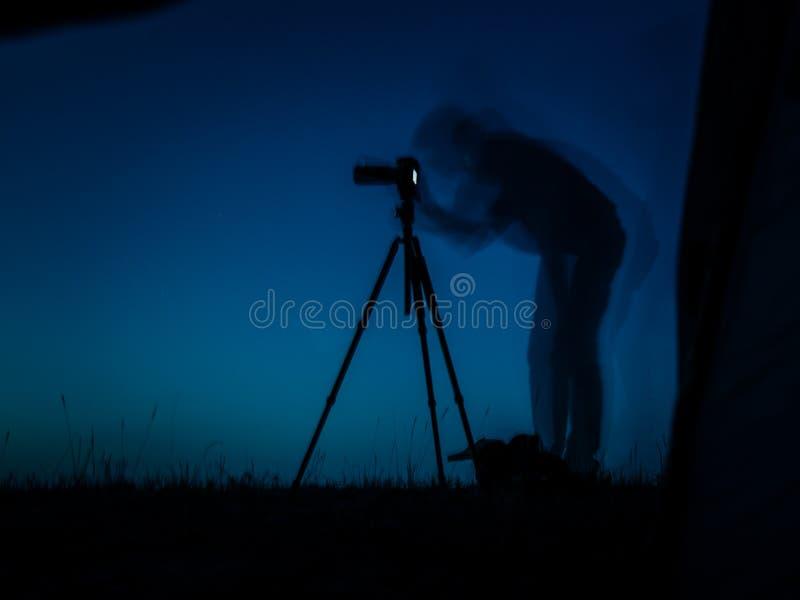 Artistieke lange blootstellingsfoto van een fotograaf in actie Veelvoudige silhouetten en een driepoot van de camerav.n. royalty-vrije stock fotografie