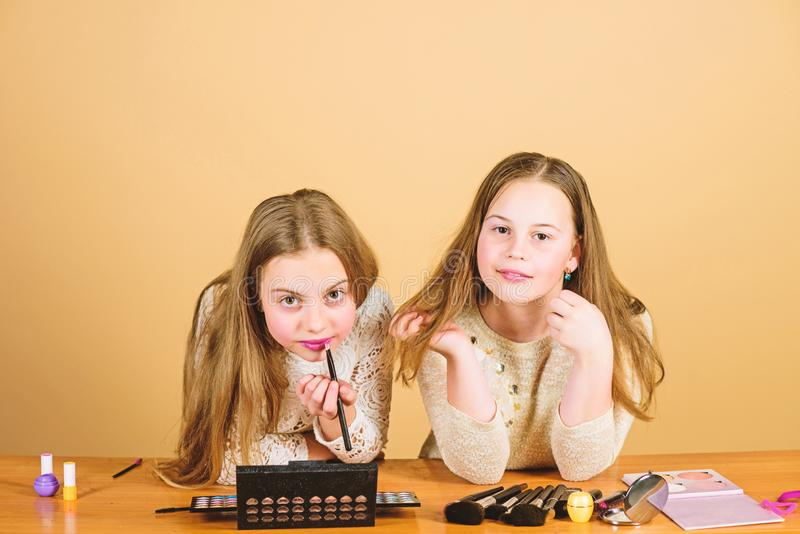 Artists helping to look good. Adorable beauty artists doing makeup. Small makeup artists giving beauty tutorial. Little. Cute make-up artists applying lipstick stock photo