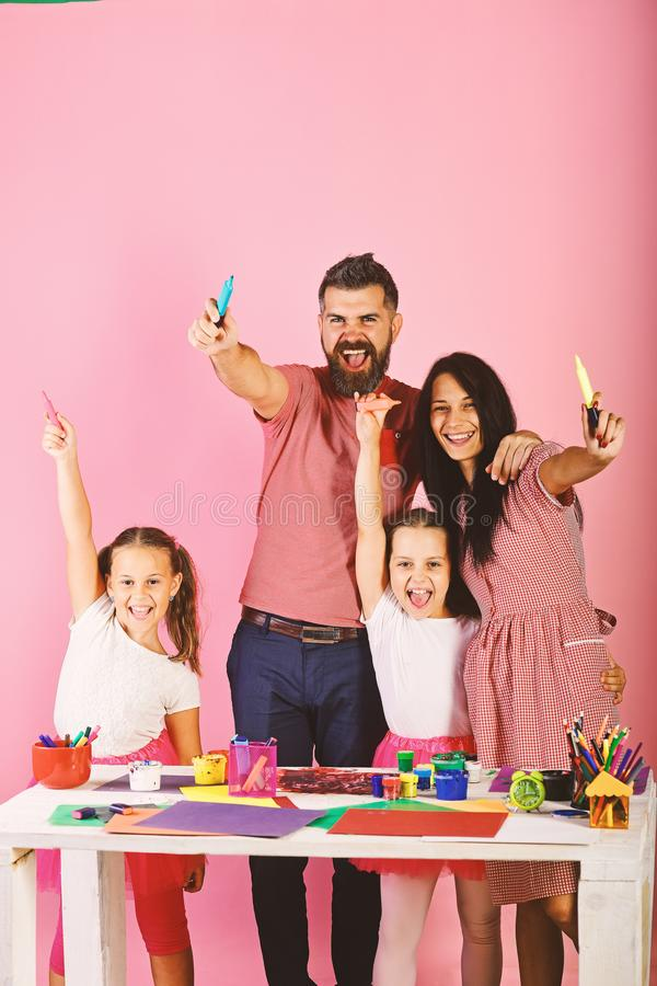 Artists hug and show colored markers. Family leisure time stock image