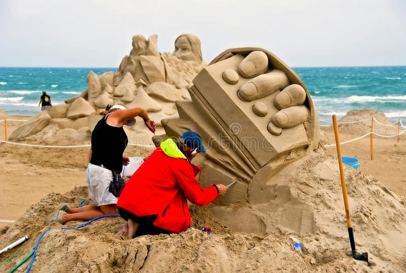 Artists work on sand sculpture stock images