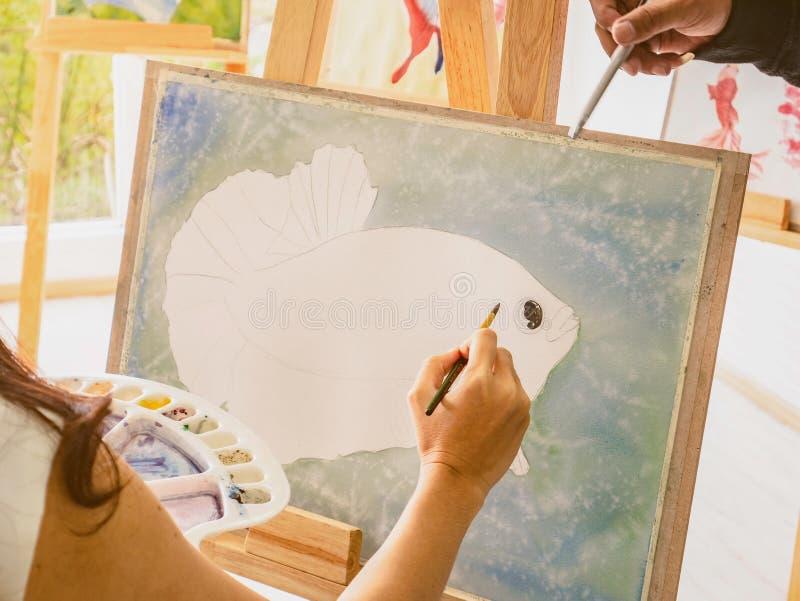Artrist asiático das mulheres que pinta os peixes na sala de aula quando seus ensino e tutor do professor como pintar fotos de stock royalty free