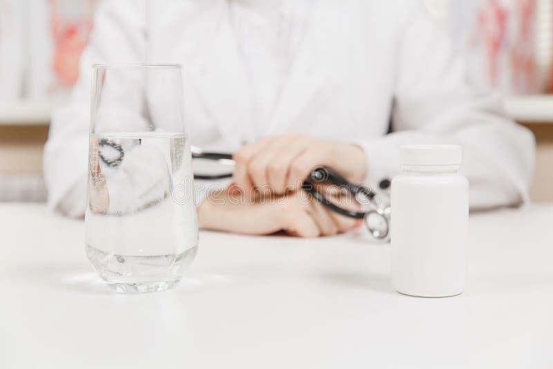 Arts bij bureau met flessen witte pillen, glas water in bureau in het ziekenhuis De vrouw houdt binnen in handenstethoscoop royalty-vrije stock foto's