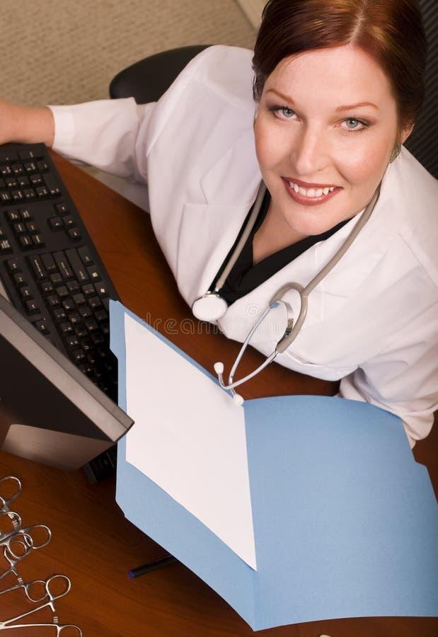 Arts bij haar Bureau stock afbeelding