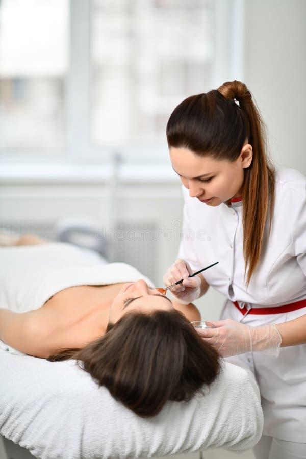 Arts-Cosmetologist bereidt patiënt voor een kosmetische procedure door een speciale samenstelling met een borstel voor zacht aan  stock afbeeldingen