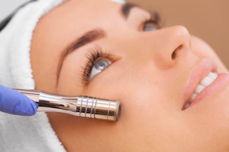 Arts-cosmetologist maakt de procedure Microdermabrasion van de gezichtshuid van een mooie, jonge vrouw in een schoonheidssalon stock foto's