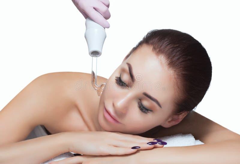 Arts-cosmetologist maakt de therapie van proceduremicrocurrent op het haar van een mooie, jonge vrouw in een schoonheidssalon stock afbeeldingen