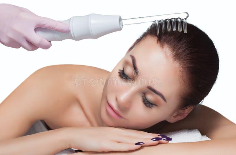 Arts-cosmetologist maakt de therapie van proceduremicrocurrent op het haar van een mooie, jonge vrouw in een schoonheidssalon stock fotografie