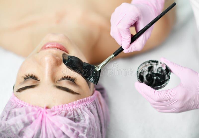Arts-Cosmetologist past met een borstel een donkere kleuren speciale deklaag op het gezicht van de patiënt toe voor een kosmetisc royalty-vrije stock afbeeldingen