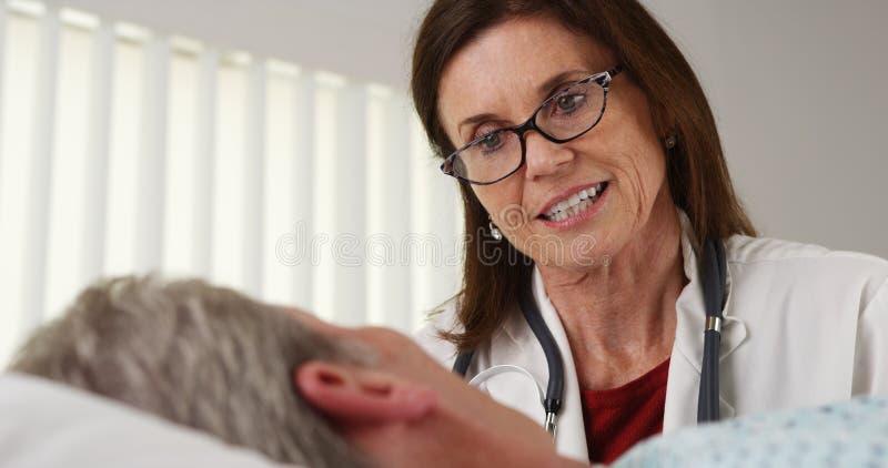 Arts die aan bejaard geduldig het ziekenhuisbed spreken stock foto's