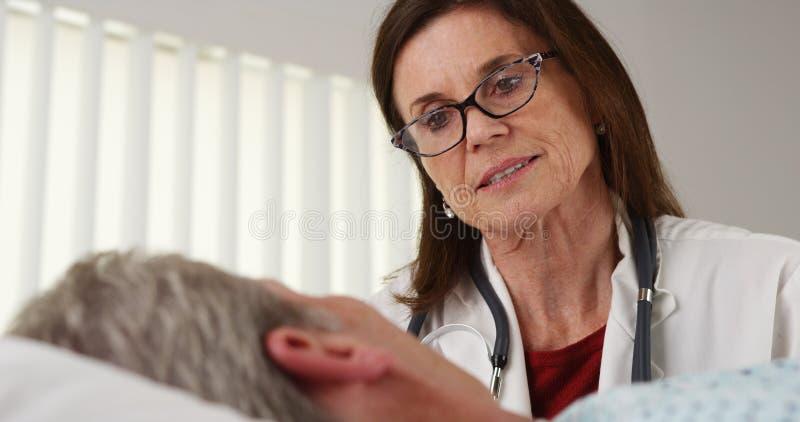 Arts die aan bejaarde patiënt spreekt royalty-vrije stock afbeeldingen