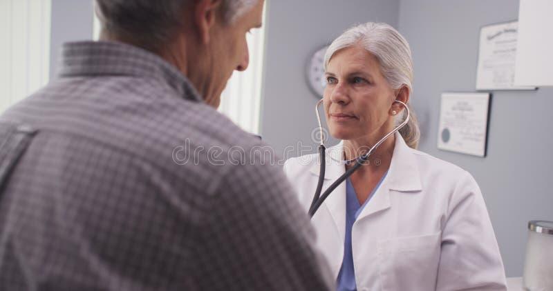 Arts die aan het harttarief van de patiënt luisteren met stethoscoop royalty-vrije stock foto's