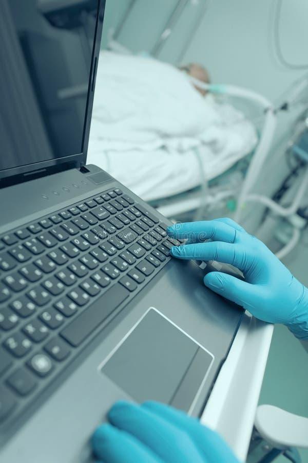 Arts die aan laptop in het intensive care werken stock foto