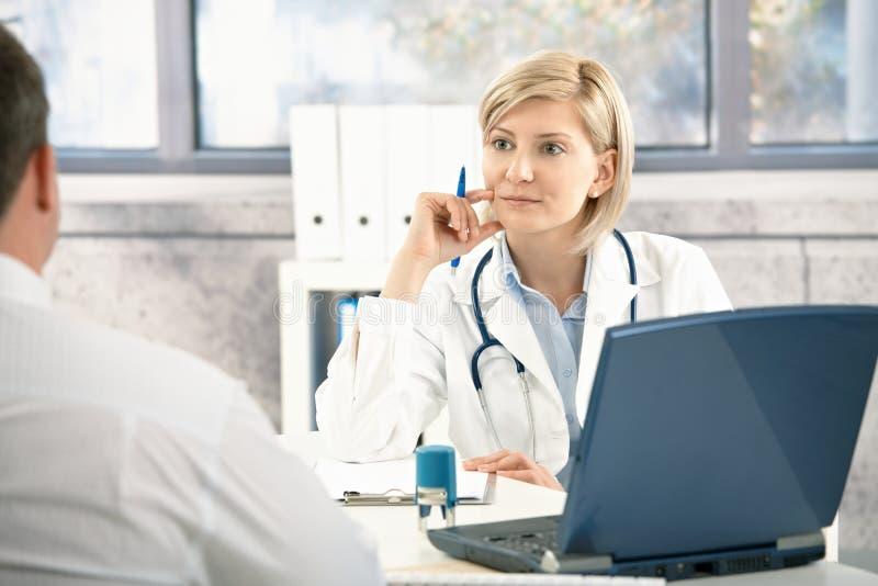 Arts die aan patiënt luistert royalty-vrije stock afbeeldingen