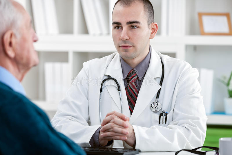 Arts die aan patiënt spreken stock afbeelding