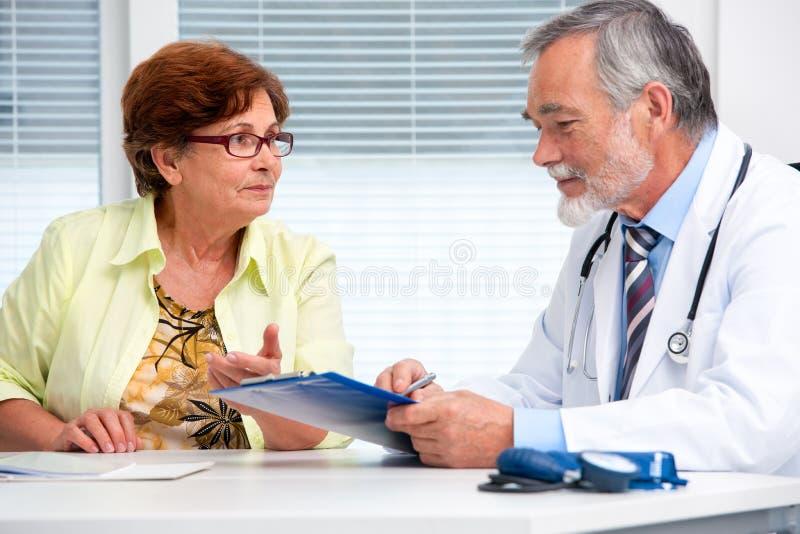 Arts die aan zijn vrouwelijke patiënt spreken royalty-vrije stock afbeeldingen