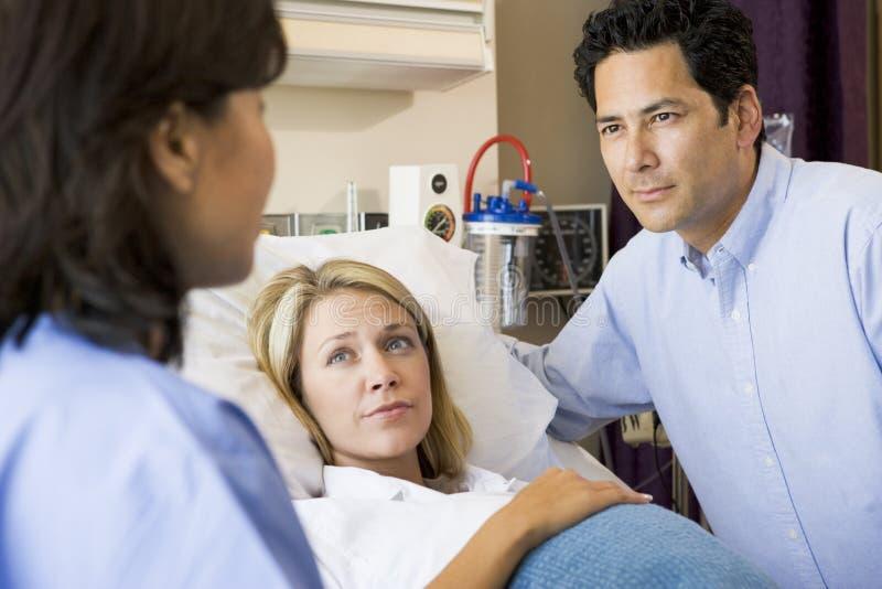 Arts die aan Zwangere Vrouw en Haar Echtgenoot spreekt stock afbeelding