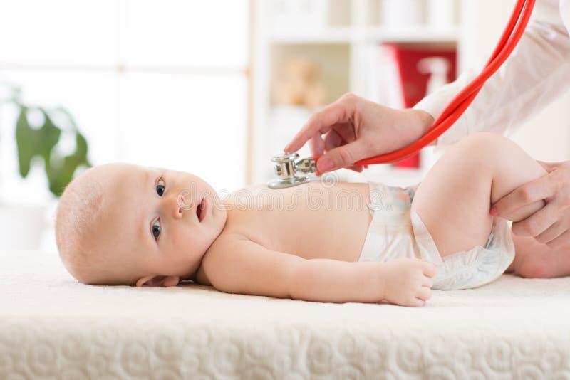 Arts die baby met stethoscoop in kliniek onderzoeken Het Concept van de babygezondheid stock foto
