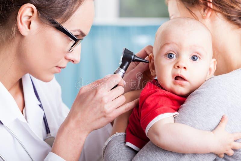 Arts die babyjongen met oorspiegel onderzoeken royalty-vrije stock afbeeldingen