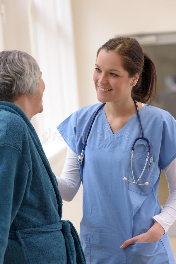 Arts die bij hogere patiënt glimlachen stock foto's