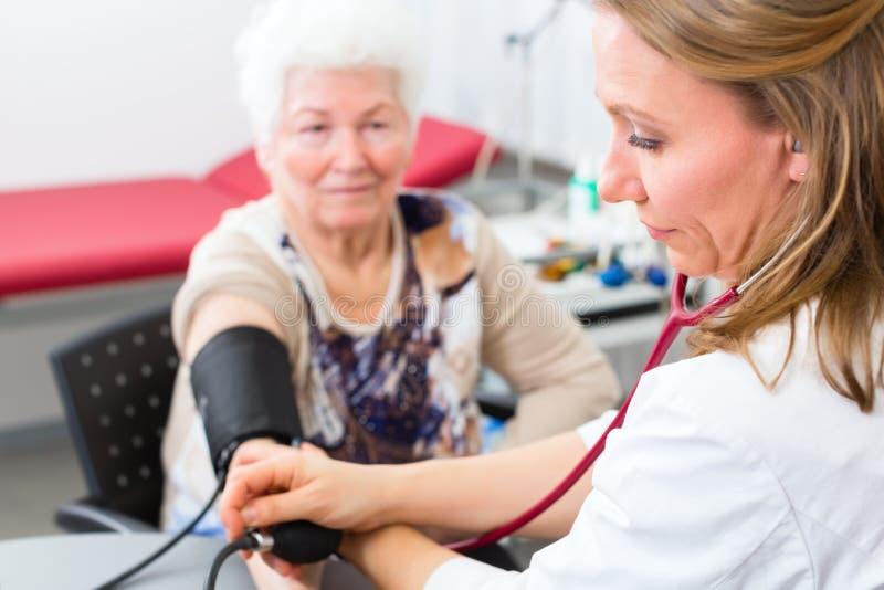 Arts die bloeddruk van hogere patiënt meten stock afbeelding