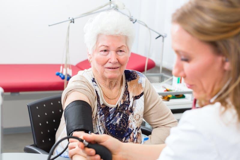 Arts die bloeddruk van hogere patiënt meten royalty-vrije stock fotografie