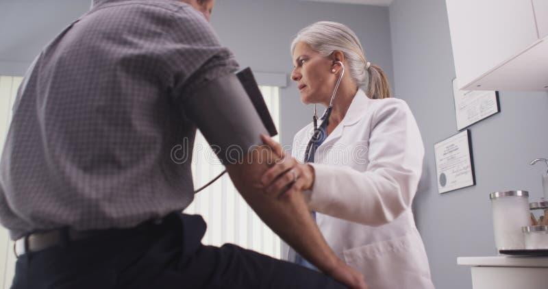 Arts die bloeddruk van mannelijke patiënt op middelbare leeftijd controleren stock afbeelding