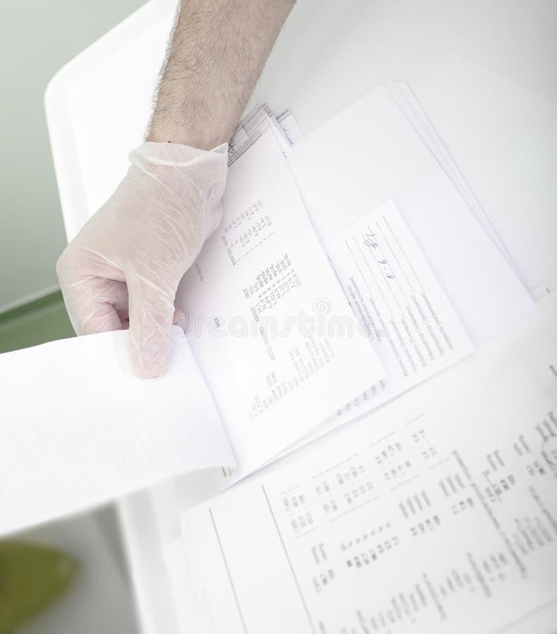 Arts die bloedonderzoeken van de patiënt doorbladeren stock fotografie