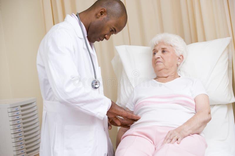 Arts die controle geeft aan vrouw in examenruimte stock foto's