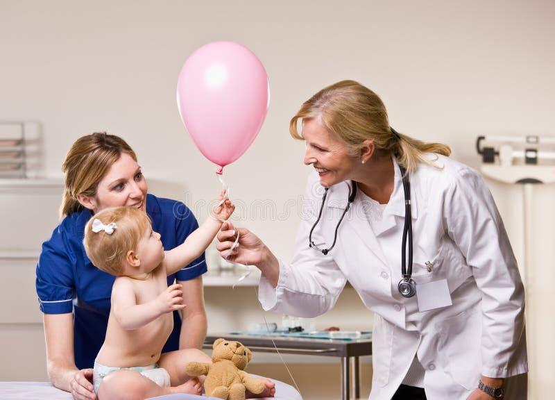 Arts die de ballon van het babymeisje overhandigt stock foto