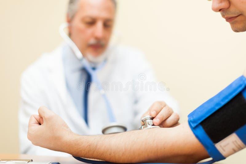 Arts die de bloeddruk meten stock afbeeldingen