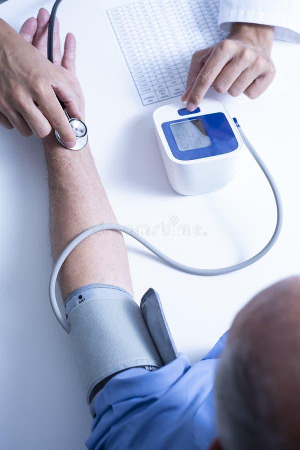 Arts die de bloeddruk van een oudste meten stock afbeelding