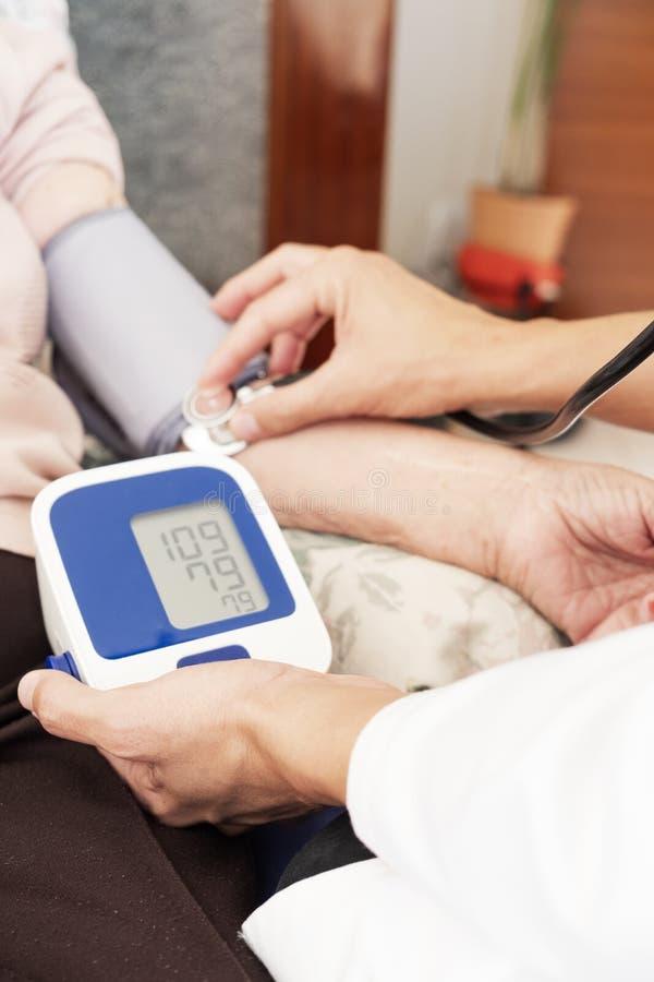 Arts die de bloeddruk van een oudste meten stock fotografie