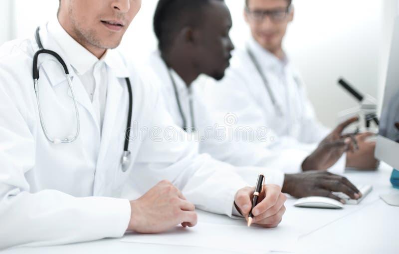 Arts die de gegevens in het laboratoriumdagboek neerschrijven stock foto's